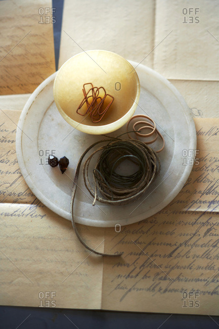 Marble plate with amber bowl with paperclips, string, rubber bands on top of old letter with fancy script