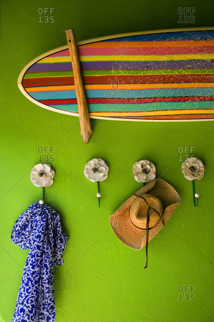 Multicolored striped surfboard hang on brilliant green wall with hooks below with hat and scarf