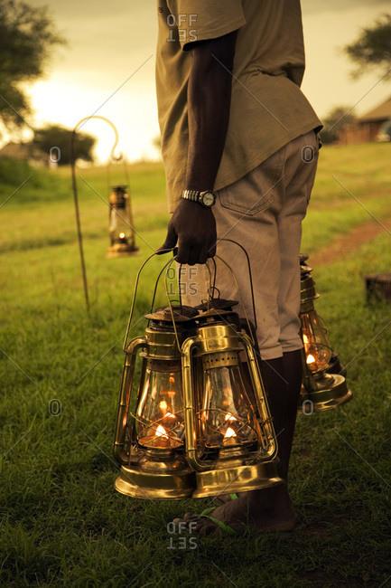 African man seen from the waist down holding lanterns