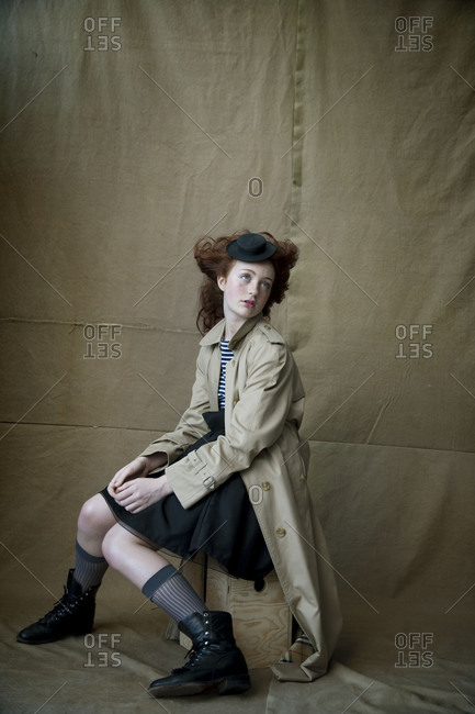Red haired girl sitting on wooden box on tan canvas backdrop wearing trench coat and tiny hat