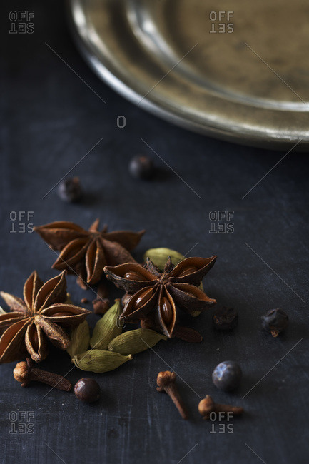 Seeds and brown star shaped pods on dark table with pewter plate