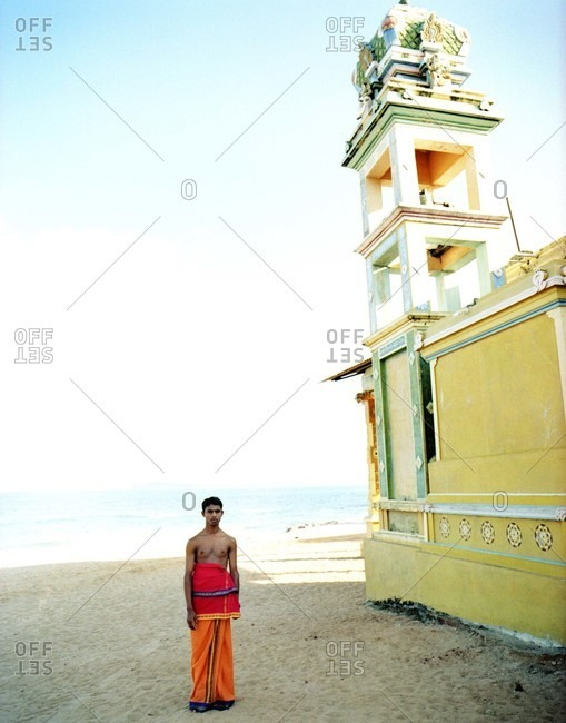Young Sri lankan man in orange and red cloth, bare chested, standing beside yellow temple on beach
