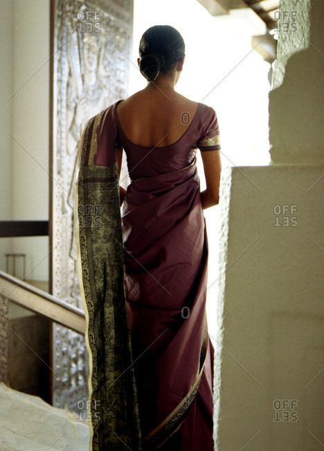 Young woman seen from behind in mauve colored sari edged in gold thread