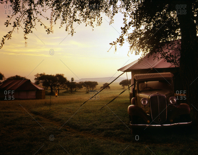 Old car on edge of safari tent camp on Serengeti Plains at dawn
