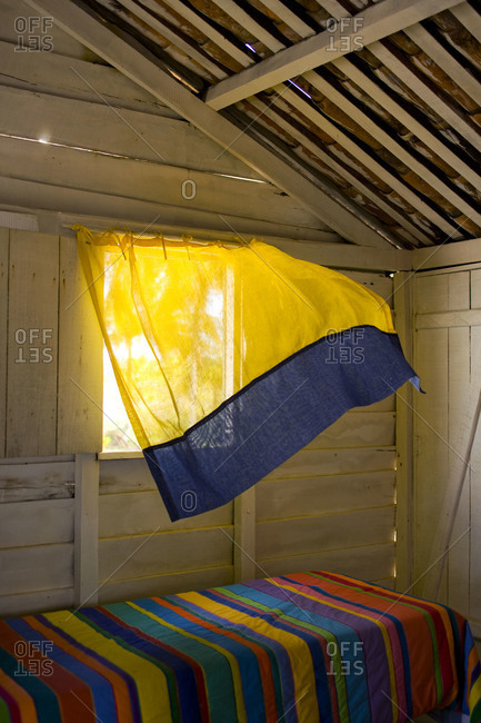 Yellow and blue curtain blows over multicolored stripe quilted bed in beach shack in Bahia, Brazil