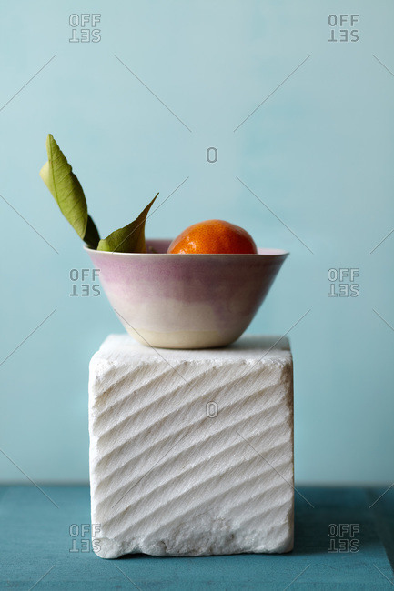 A marble block with serrated edge shown with violet colored bowl and orange inside with leaf attached on aqua background