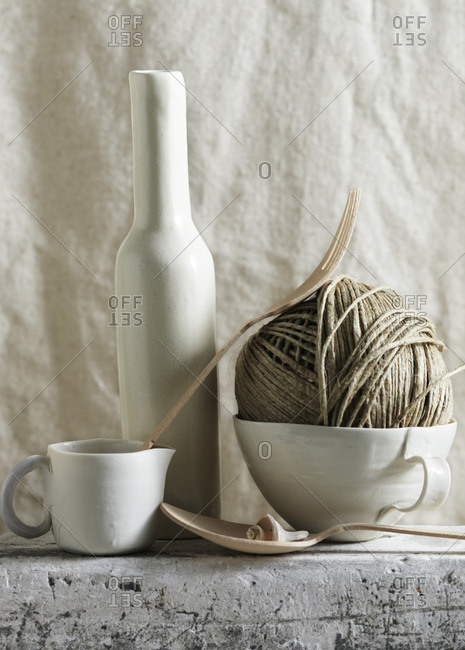 Two white tea cups, white vase and string with wooden spoon on stone surface with canvas backdrop