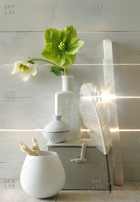 White vase and assorted objects on white wall