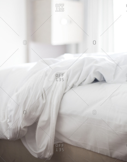 An unmade bed in a white room
