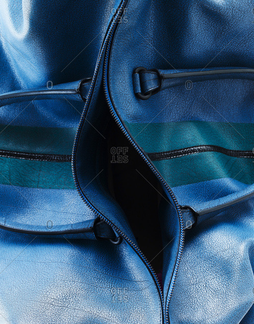 A blue cowhide leather handbag with a green stripe.