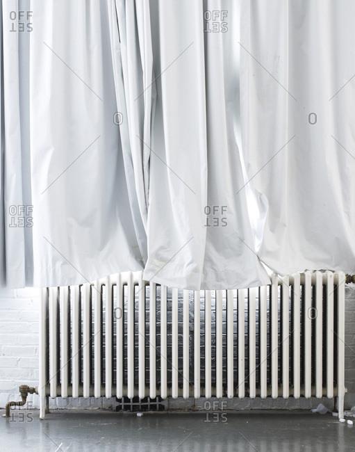 Cast iron radiator with white curtain