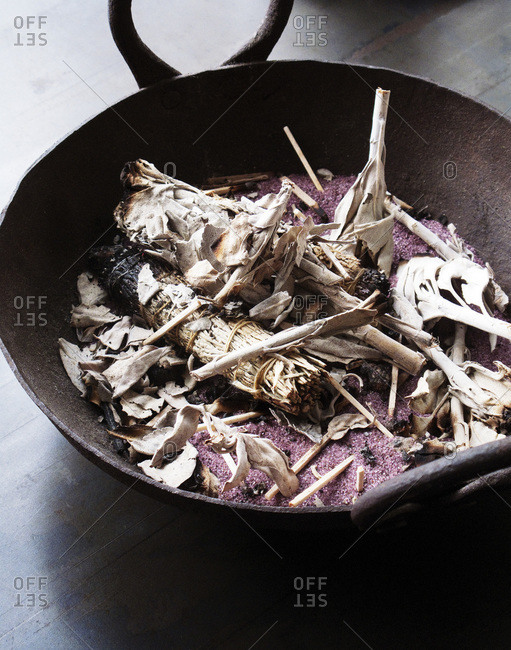 Ashes and burnt dried leaves in an iron cast bowl