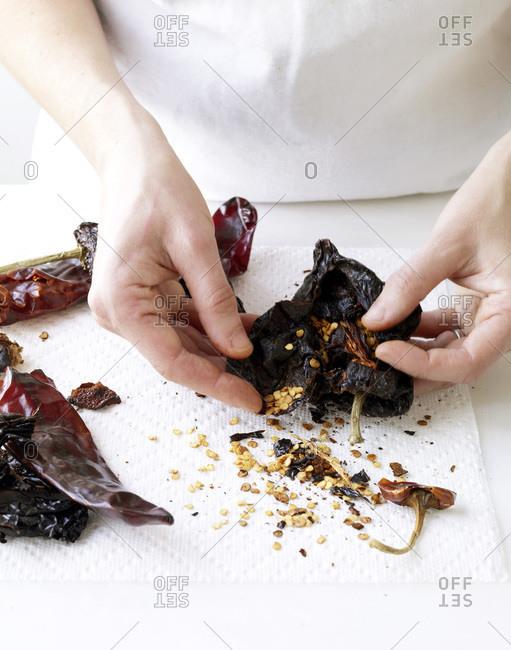 Hands peeling roasted pepper
