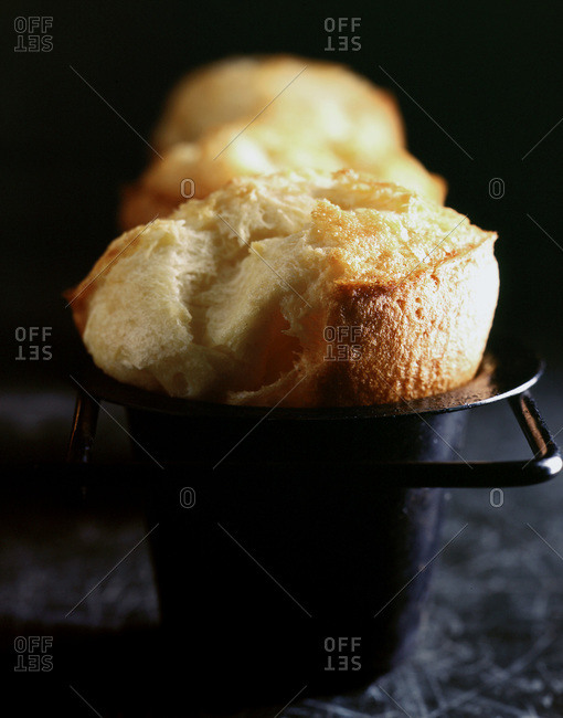 Swelled, freshly baked popovers in muffin tin.