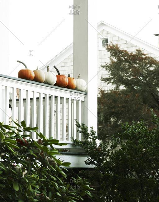 Pumpkins sitting on white banister.