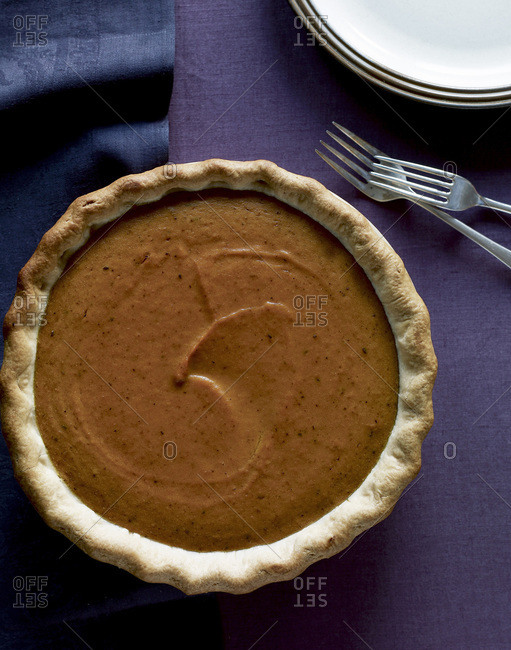 Tempting pumpkin pie on a table from above.
