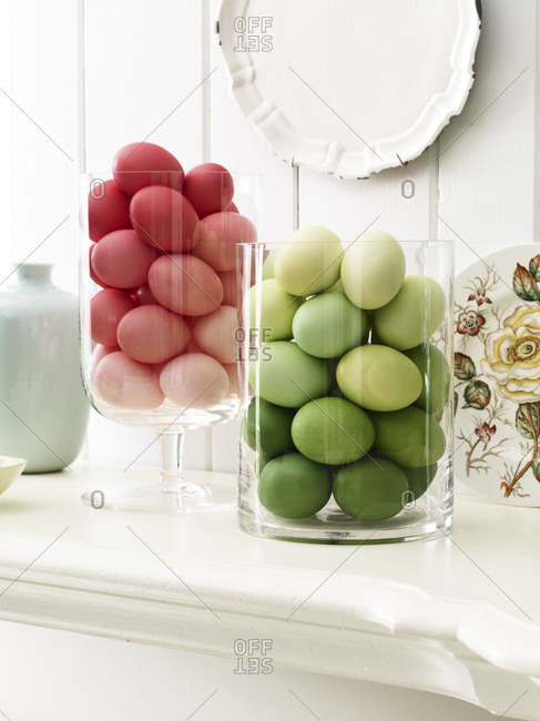 Colorful easter eggs in glass containers on a mantle