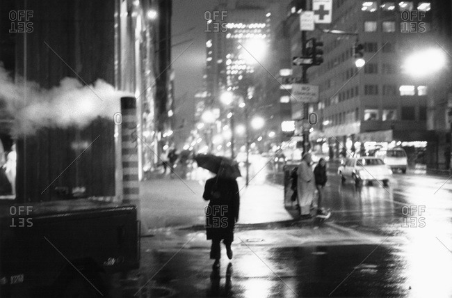 A person crossing a New York city street with an umbrella at night