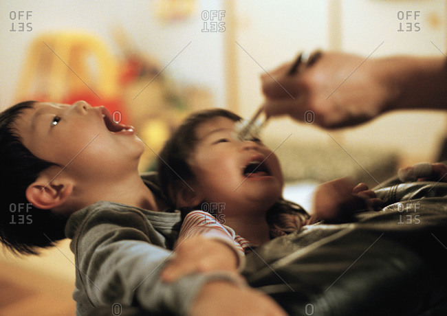 children with mouths open waiting for food from chopsticks