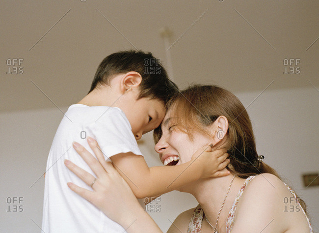 mother holding up child, laughing