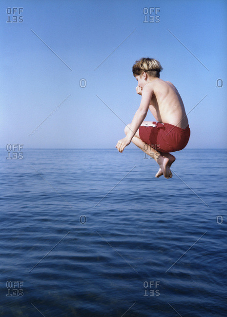 A boy in midair, jumping in the water