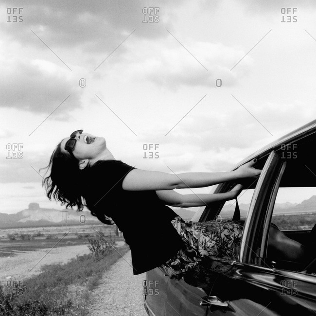 A woman hanging out a moving car window