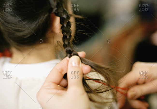 woman braiding girl's hair
