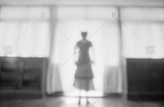 A woman standing in a bright doorway