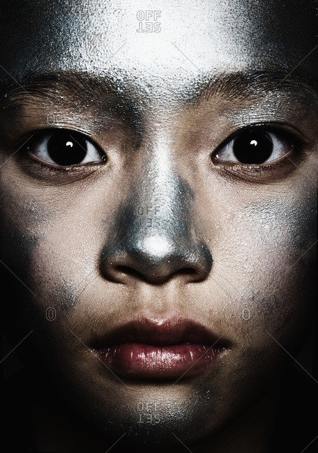 Portrait of a teenage girl with silver paint on her face