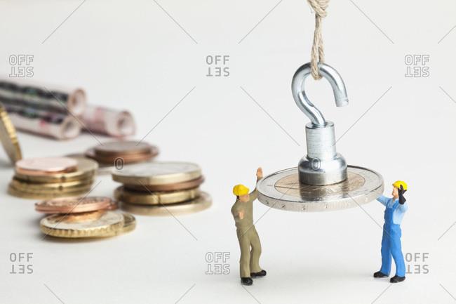Miniature workmen guiding a hanging two Euro coin down