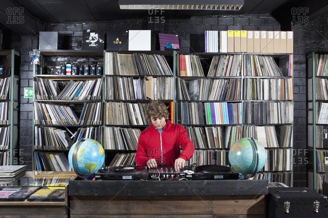 A young man using a sound mixer and DJ decks at a record store