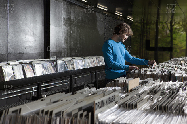 A young man searching through records in a record store