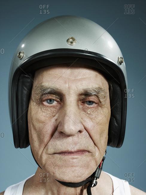 A headshot of a frowning senior man wearing a crash helmet