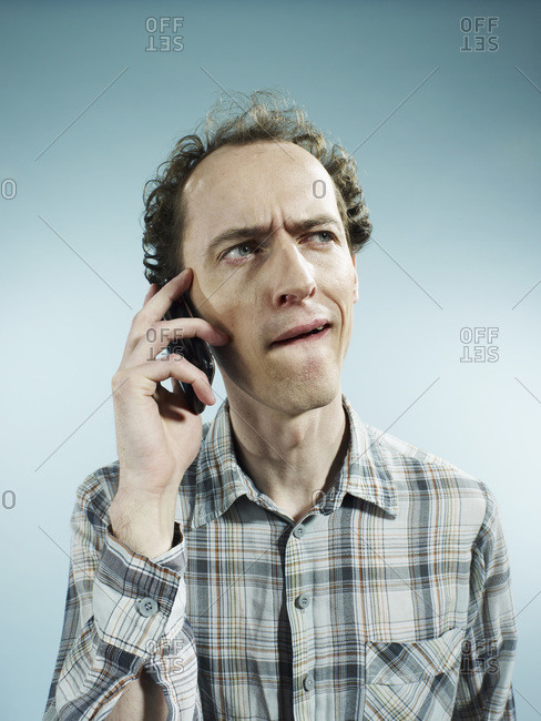 A man using a mobile phone with a confused look on his face