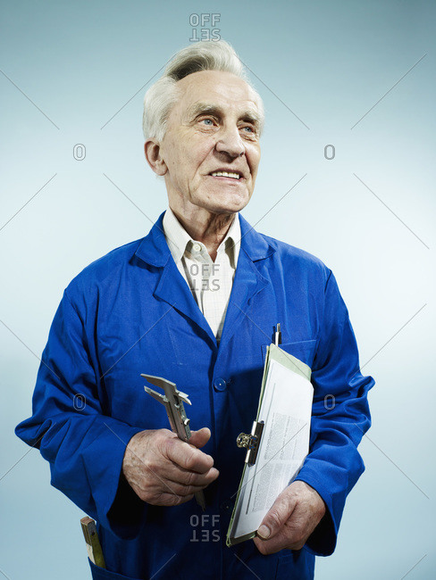 A cheerful senior man in coveralls carrying a clipboard and work tool