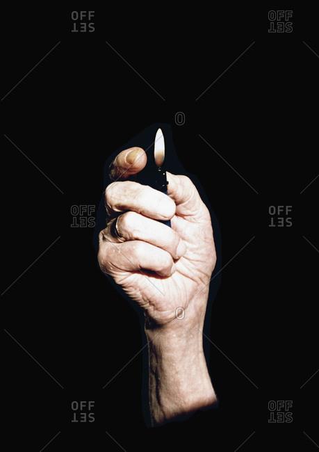 Senior woman holding a lighter