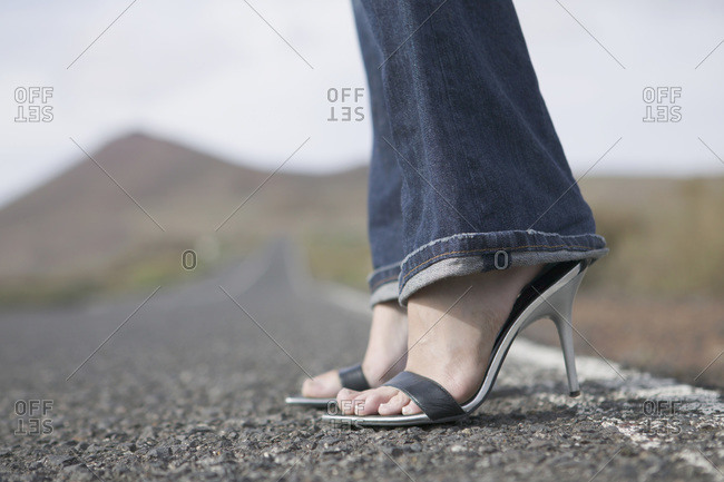Young woman stands waiting by roadside