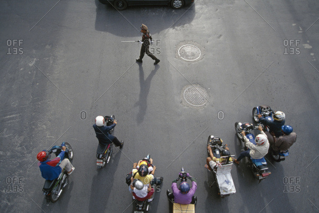 People riding motor scooters on city street, Hong Kong, Central District, China