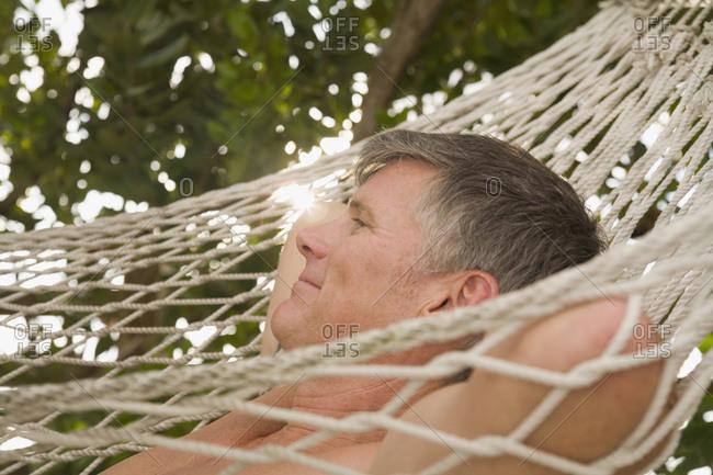 Mature man lying down on hammock