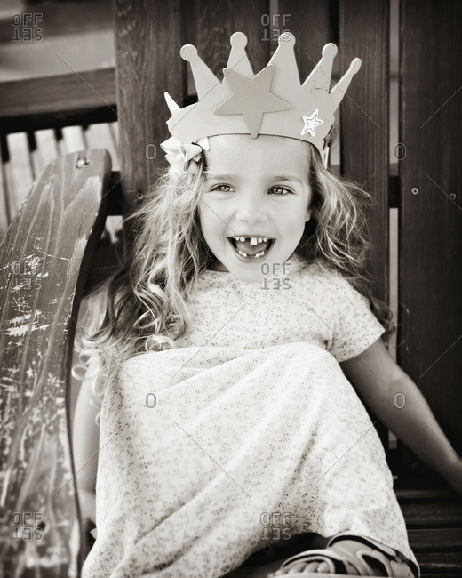 Young girl sitting in a wooden chair and wearing a crown