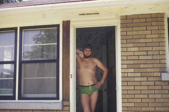 Man standing in a doorway wearing racing briefs