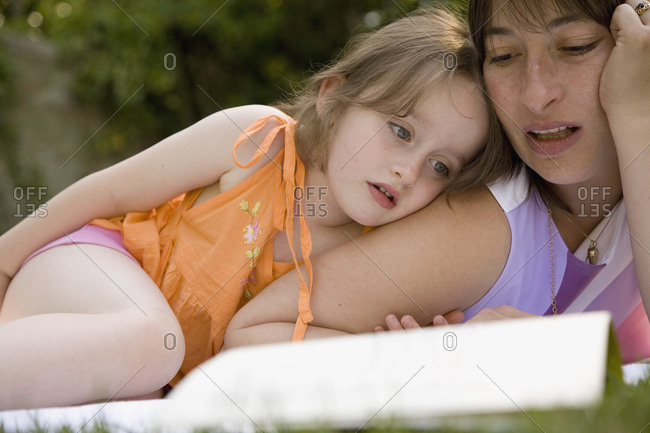 Mother and daughter lying down and reading a book together in a backyard