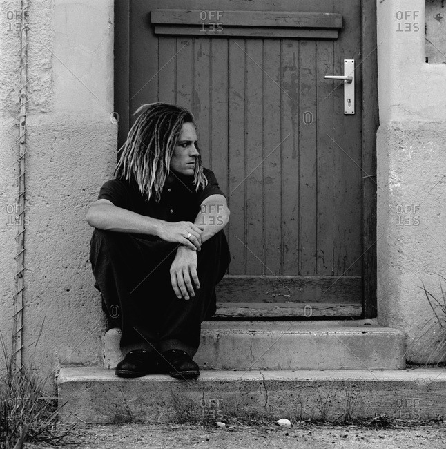 Young man with dreadlocks sitting on a doorstep