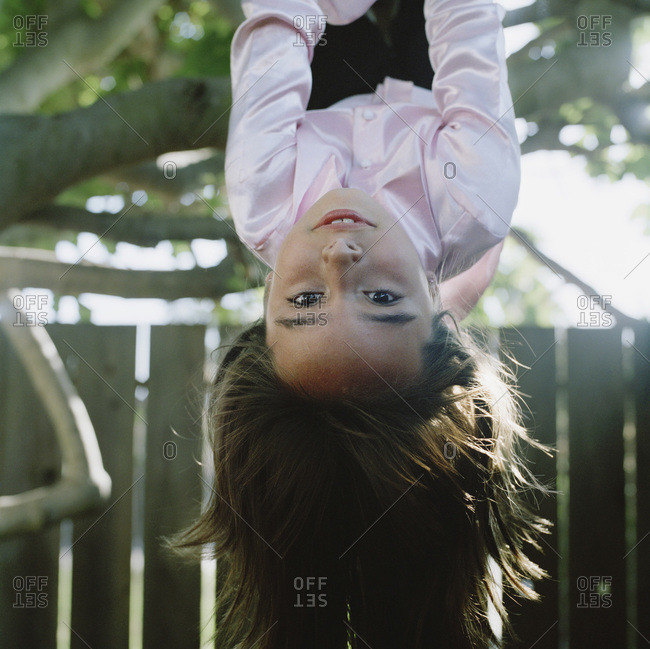 Girl hanging upside down from a tree