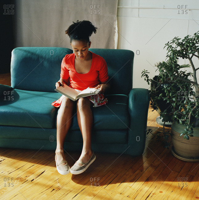 Teenage girl sitting on sofa reading