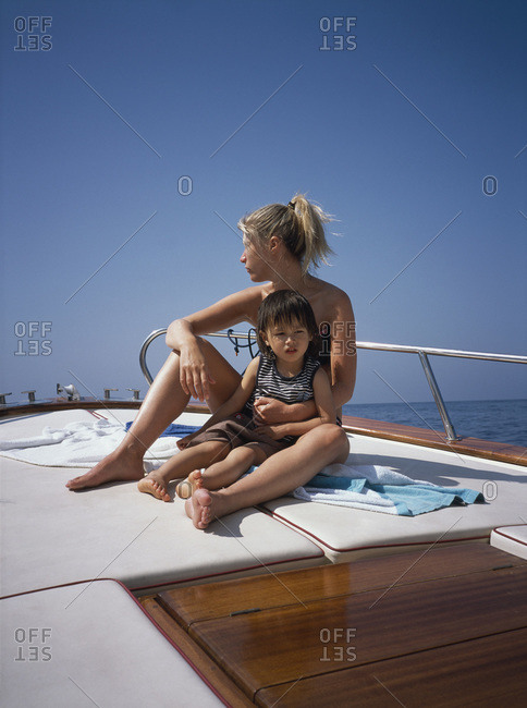 A mother and son sitting on  a boat deck