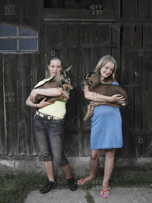 Two girls holding kid goats