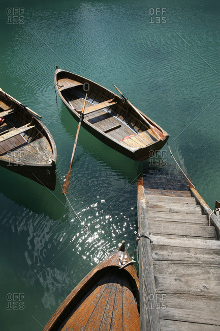 Steps down to wooden boats floating on water, Braies Lake, South Tyrol, Italy
