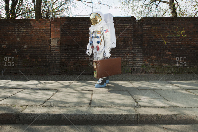 An astronaut carrying a suitcase and walking on a city sidewalk