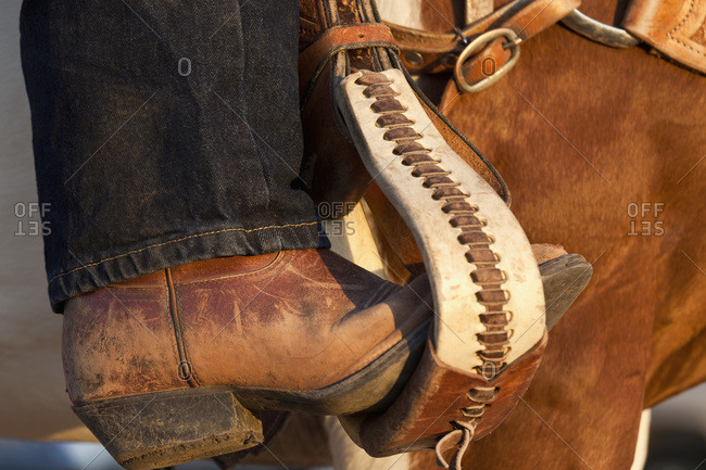 A cowboy boot in a horse stirrup, detail